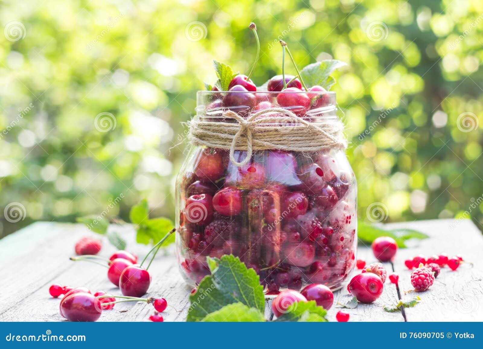 Le pot en verre porte des fruits des cerises et des framboises