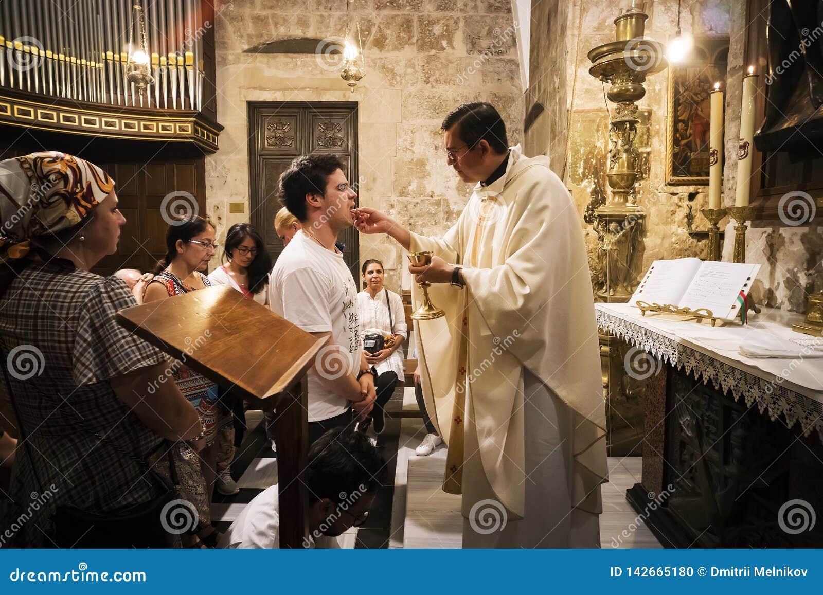 Le prêtre de l église de la tombe sainte donne la sainte communion à l homme fidèle avec d autres croyants attendant leur tour jé