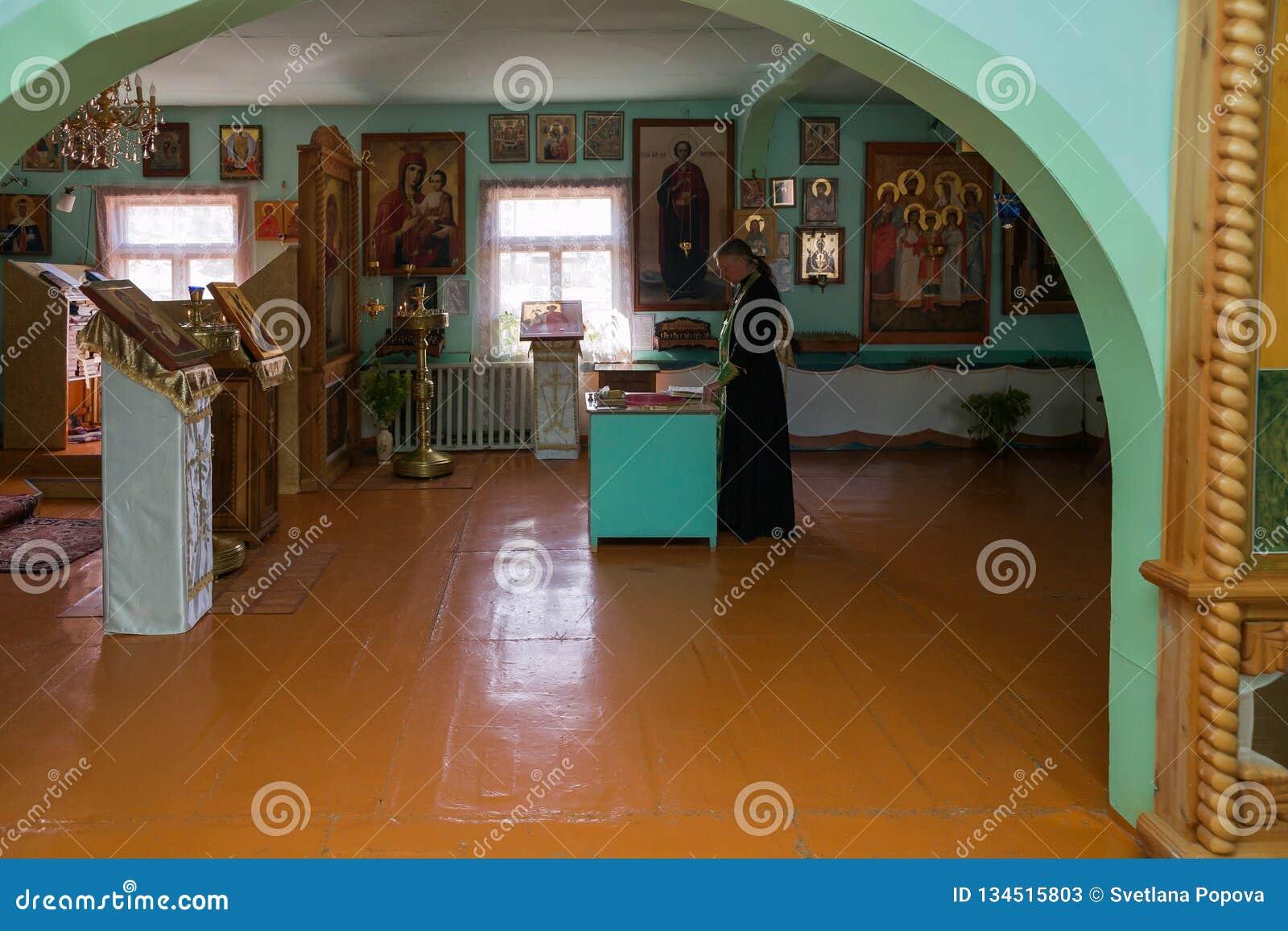 Le prêtre lit une prière devant l autel à l intérieur de l église russe de village