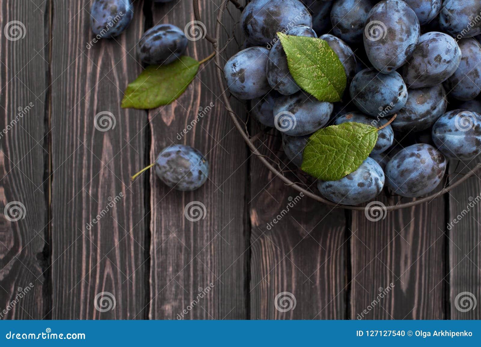 Le prugne blu del giardino in una ciotola su un fondo di legno rustico scuro con la copia spaziano la vista superiore Fotografia Stock
