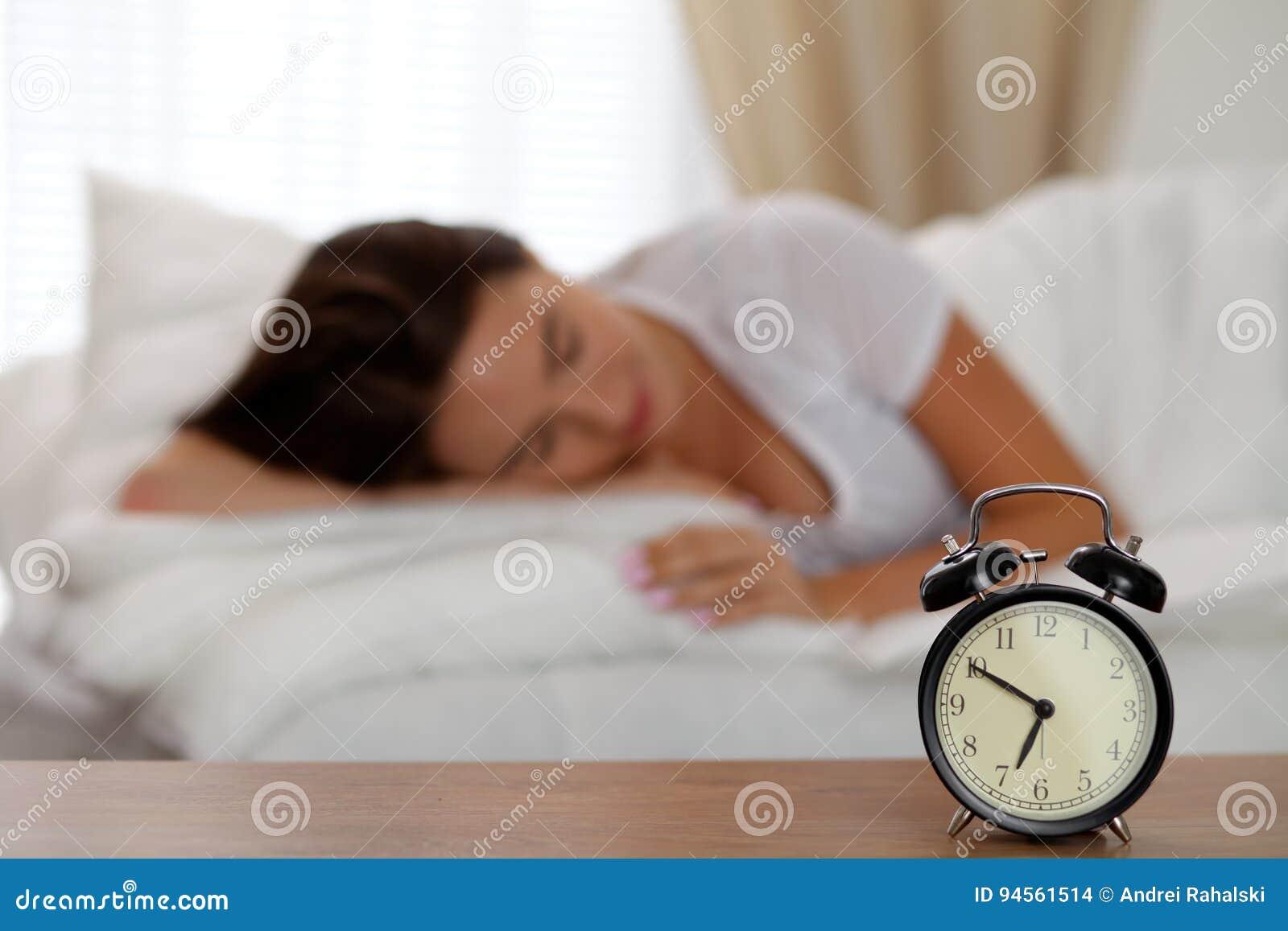 Le réveil se tenant sur la table de chevet a déjà sonné le début de la matinée pour réveiller la femme dans le lit dormant à l ar