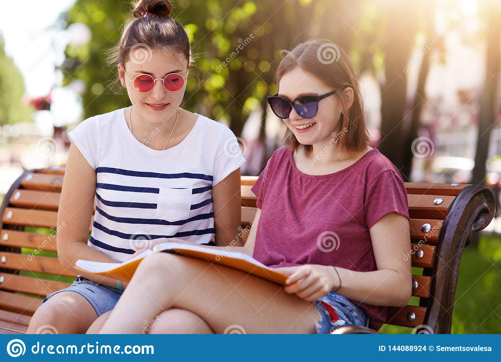 Le ragazze allegre passano insieme il tempo nel giorno soleggiato caldo nel parco Le bellezze guardano attraverso la rivista dell
