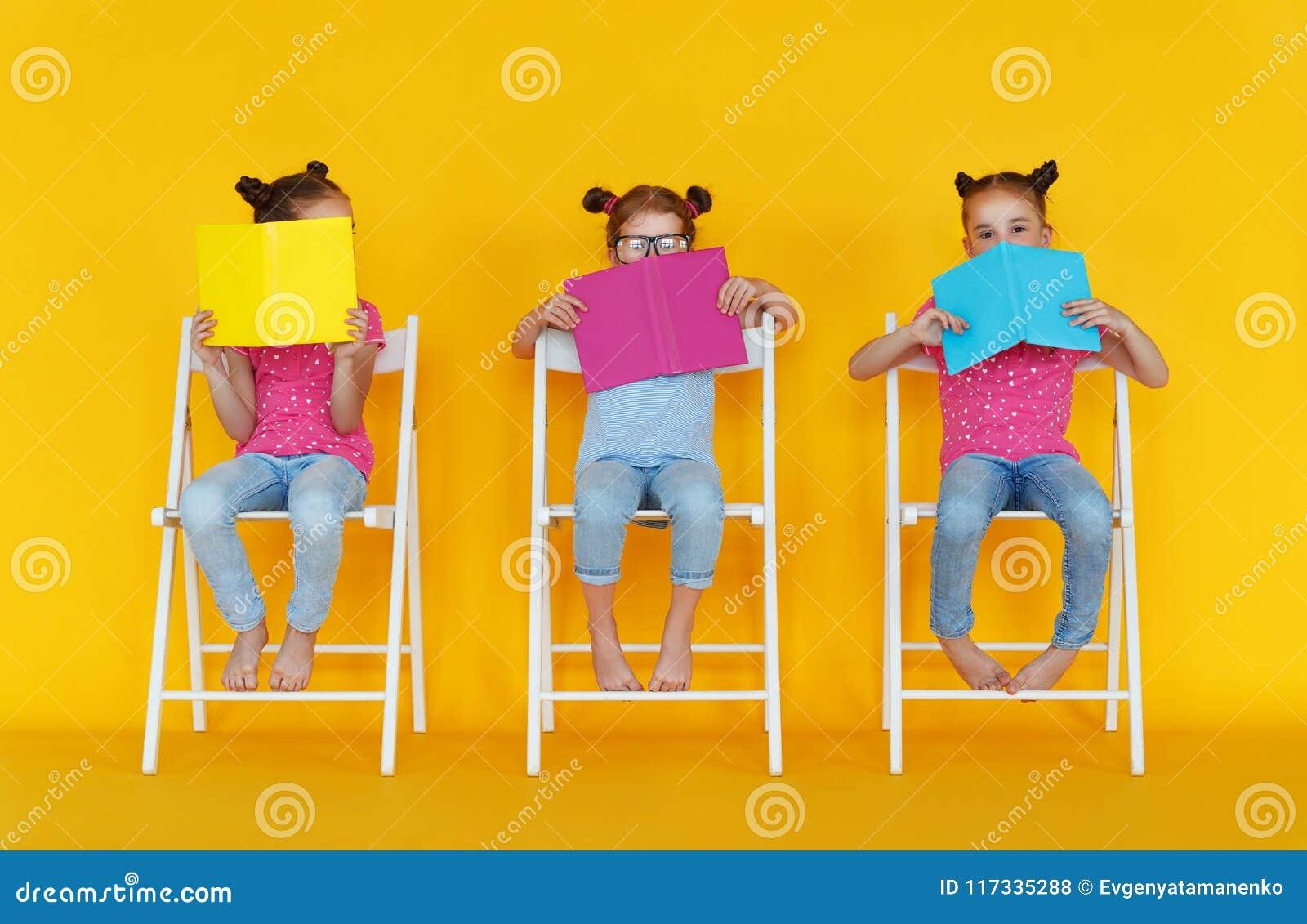 Le ragazze divertenti dei bambini hanno letto i libri su fondo giallo colorato