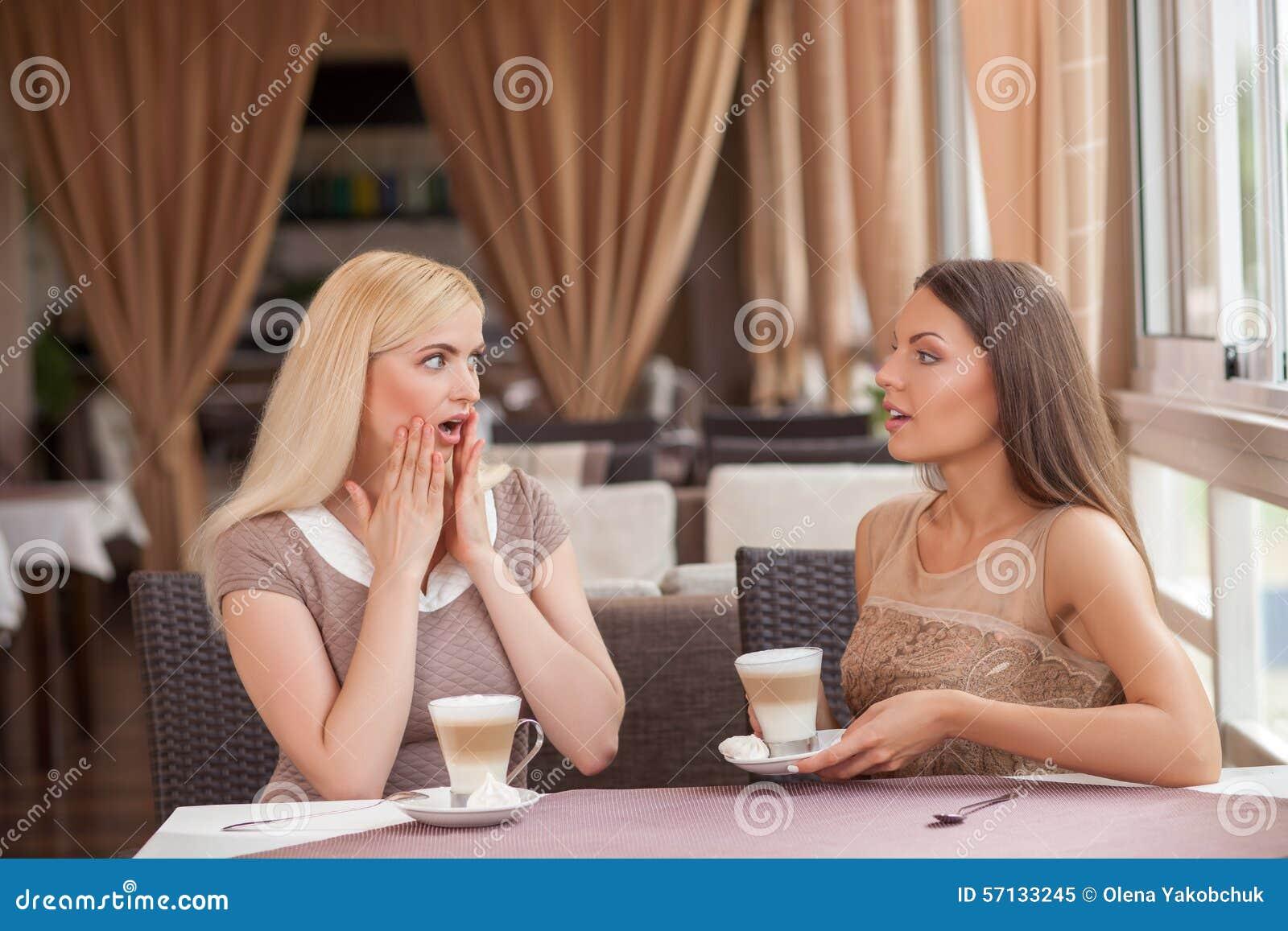 Le ragazze graziose stanno pettegolando nel self-service