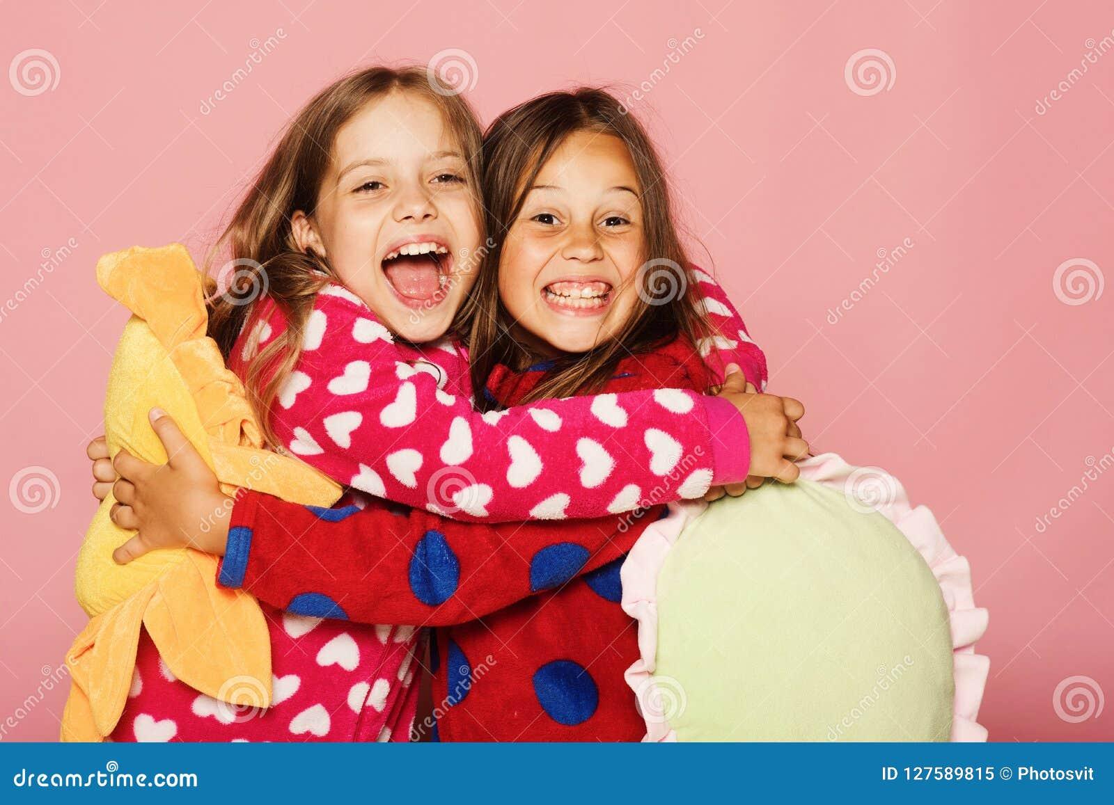 Le ragazze in pigiami punteggiati Polka variopinta tengono i cuscini luminosi divertenti