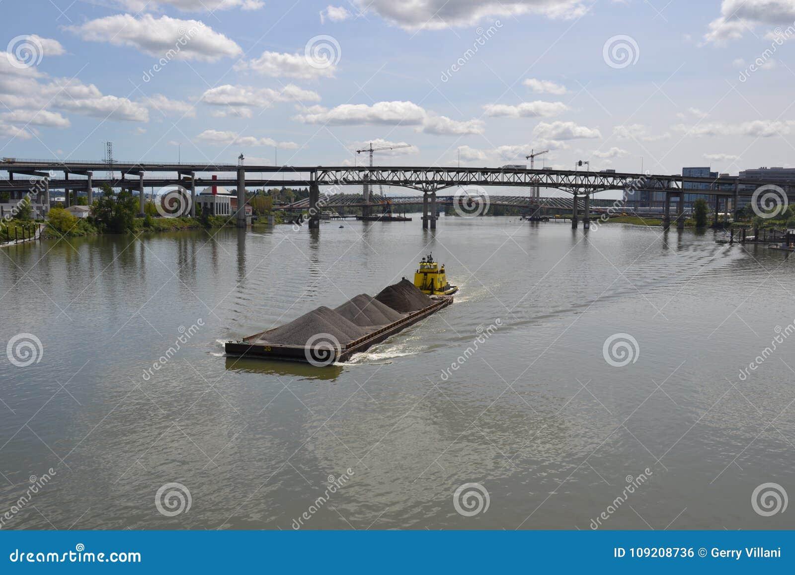 Le remorqueur jaune pousse la péniche dedans Portland, Orégon