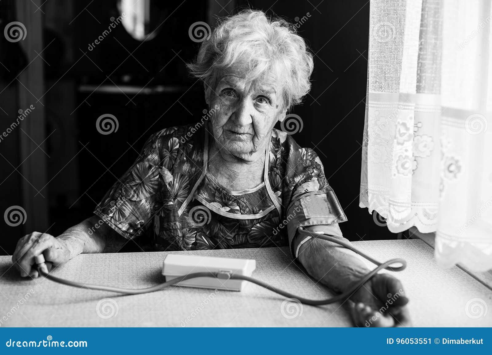 Le retraité de femme agée mesure la tension artérielle elle-même