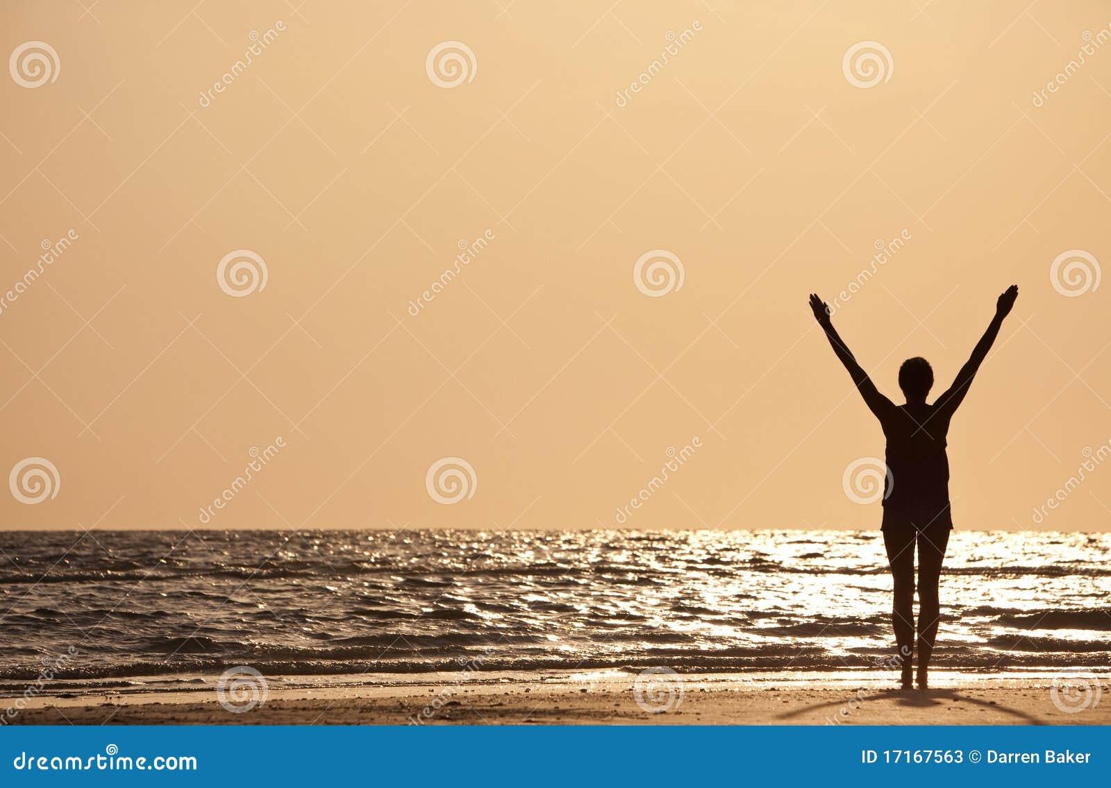 Le riuscite braccia della donna si sono alzate al tramonto sulla spiaggia