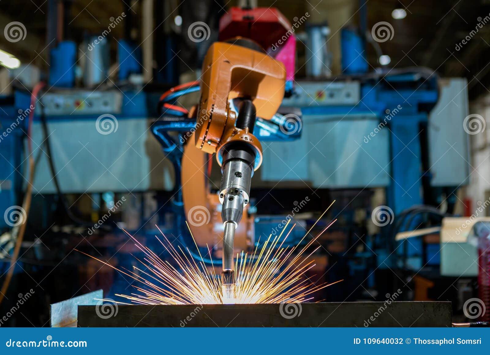 Le robot industriel en gros plan soude dans une usine de voiture