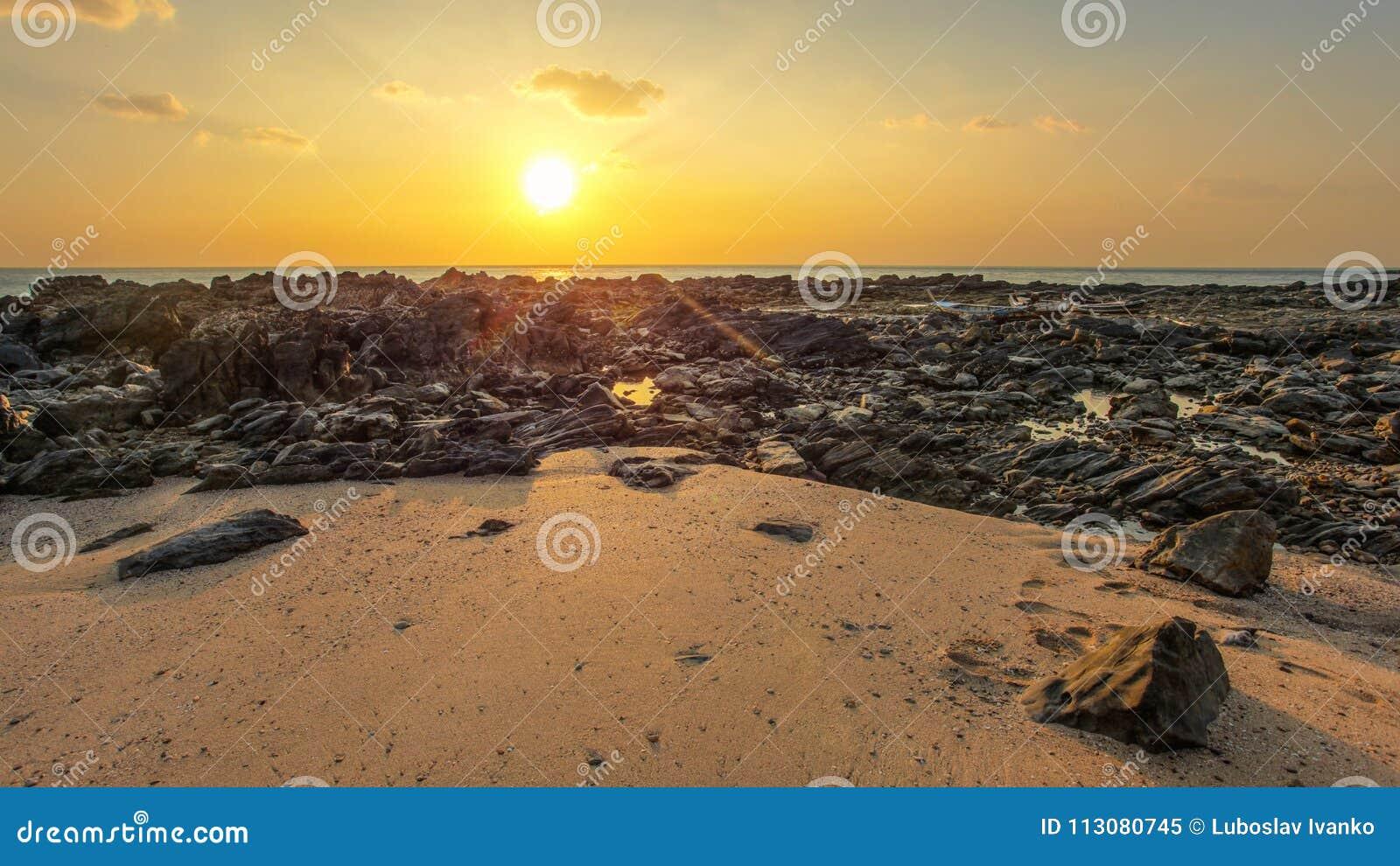 Le rocce e la spiaggia sabbiosa hanno scoperto nella bassa marea con le barche