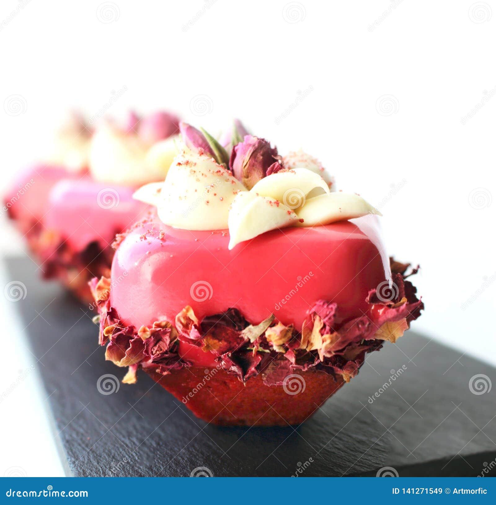 Le rose a monté des desserts avec de la crème blanche de chocolat et les pétales secs