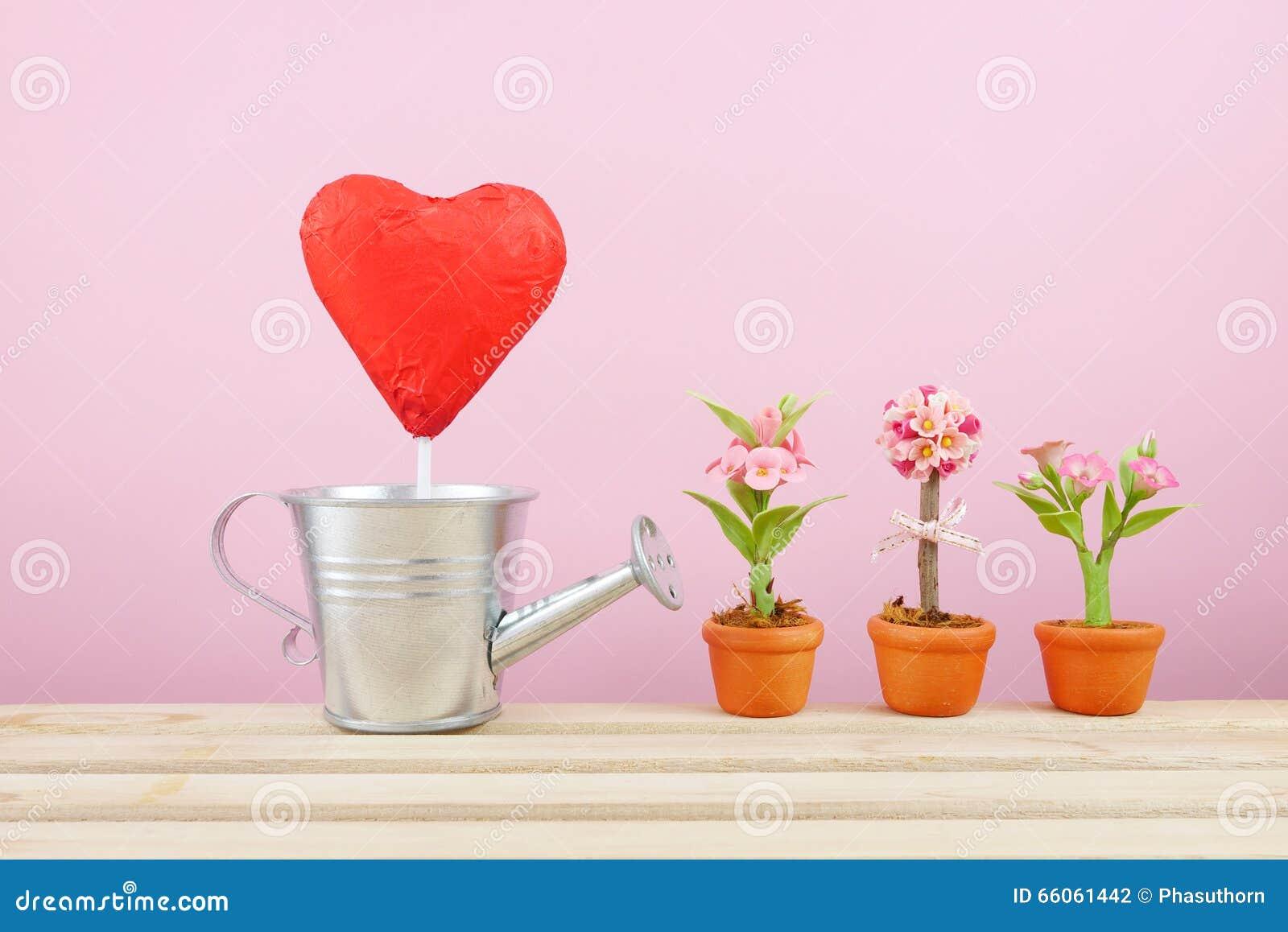 Le rouge a déjoué le bâton de coeur de chocolat avec la petite boîte d arrosage argentée et la mini fausse fleur dans le pot brun