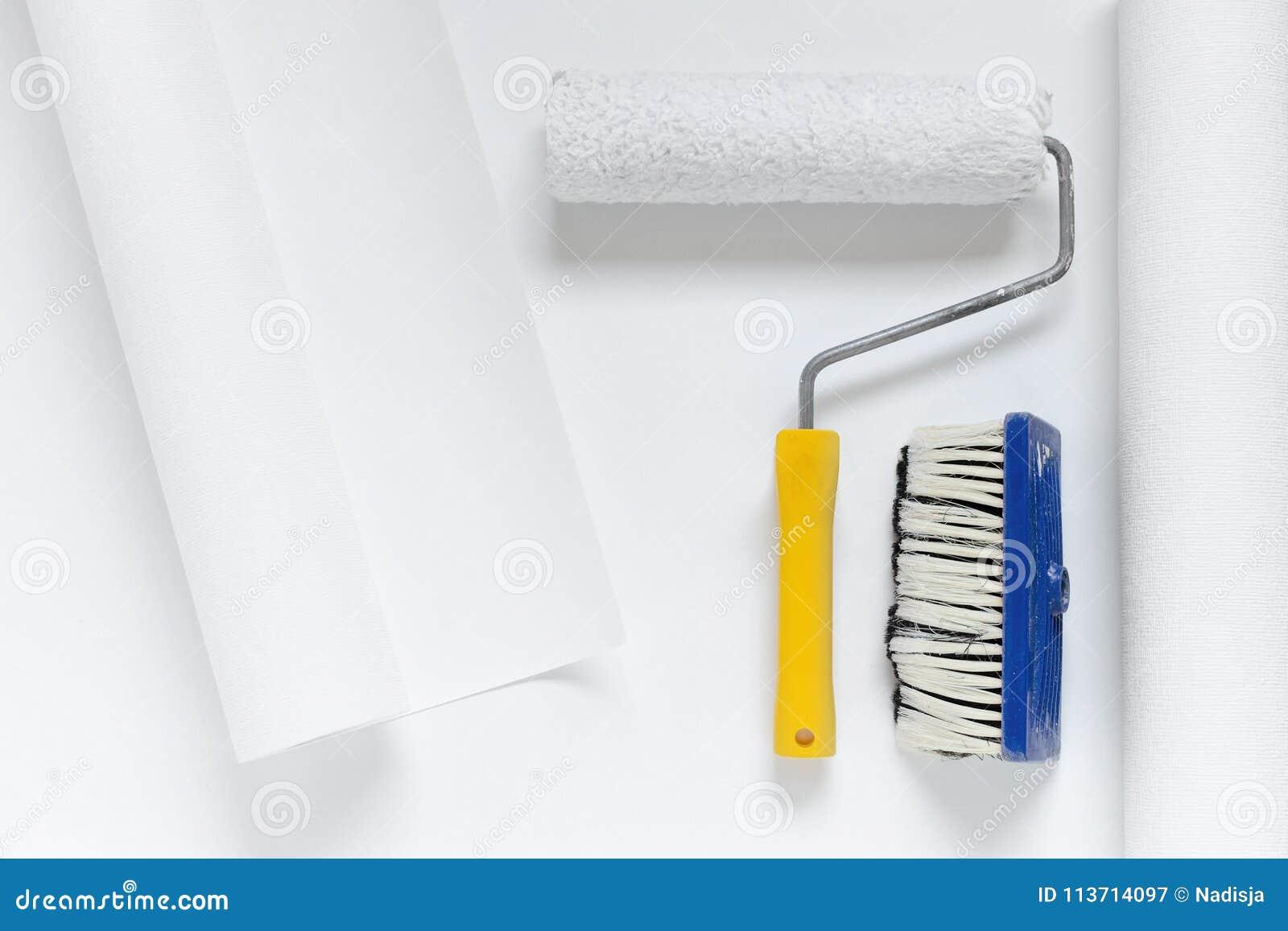 Le Rouleau De Peinture Et Une Brosse Sur Le Papier Peint Blanc