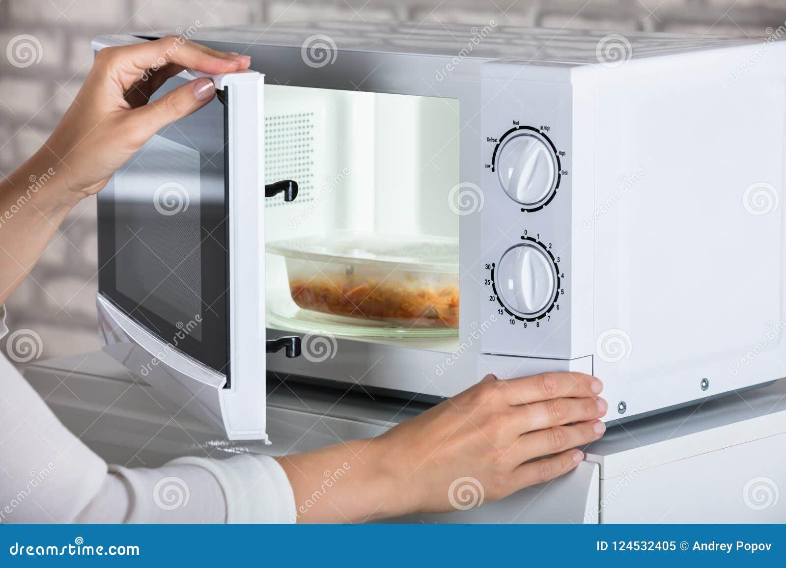 Le ` s de femme remet la micro-onde fermante Oven Door And Preparing Food