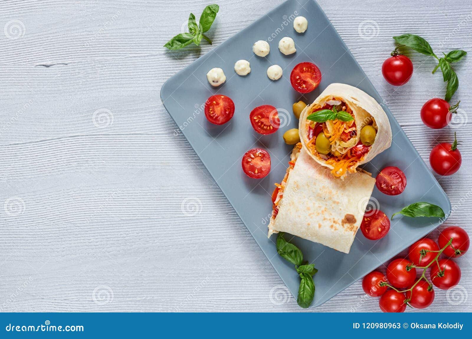 Le sandwich à Shawarma ou le pain de lavash avec les légumes frais et la sauce du plat gris decotated avec des tomates-cerises, b