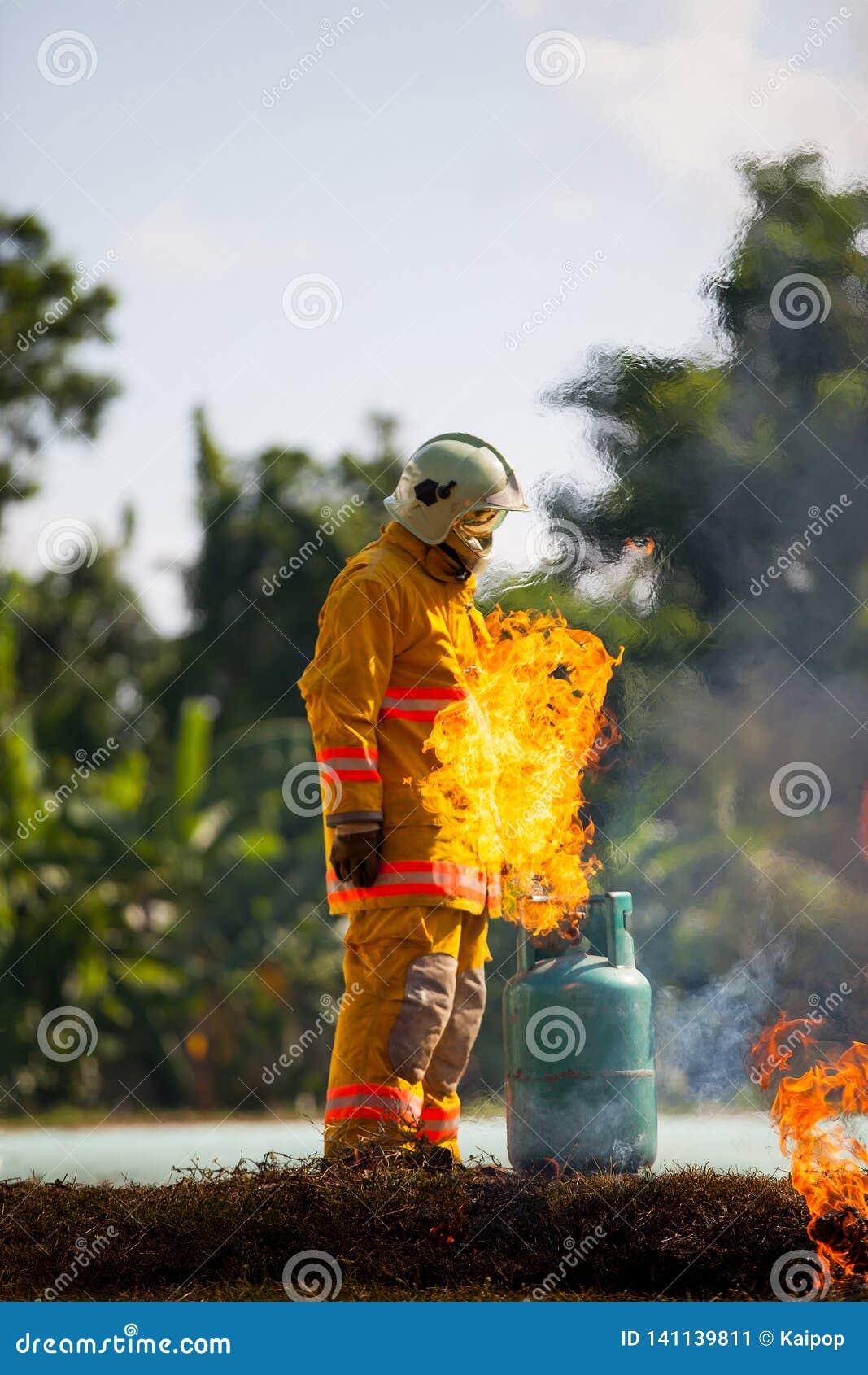 Le sapeur-pompier avec le feu et le costume pour protègent le pompier pour les sapeurs-pompiers s exerçants