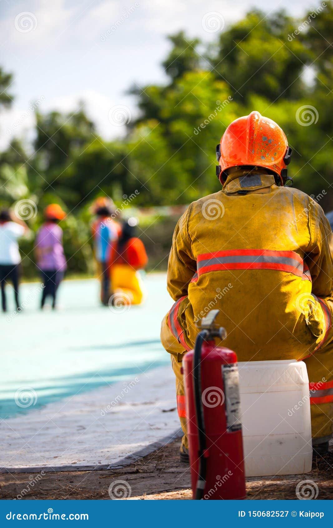 Le sapeur-pompier avec le feu et le costume pour prot?gent le pompier pour les sapeurs-pompiers s exer?ants