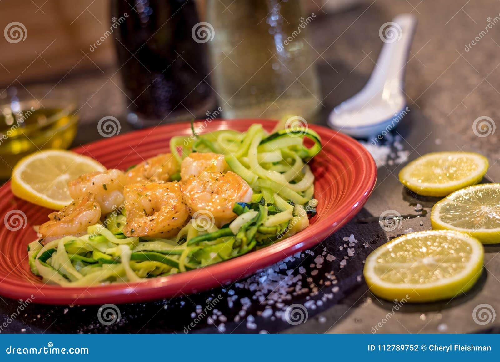 Le scampi de crevette a servi au-dessus des nouilles de courgette faites sauter avec le citron, l ail, le beurre et les herbes