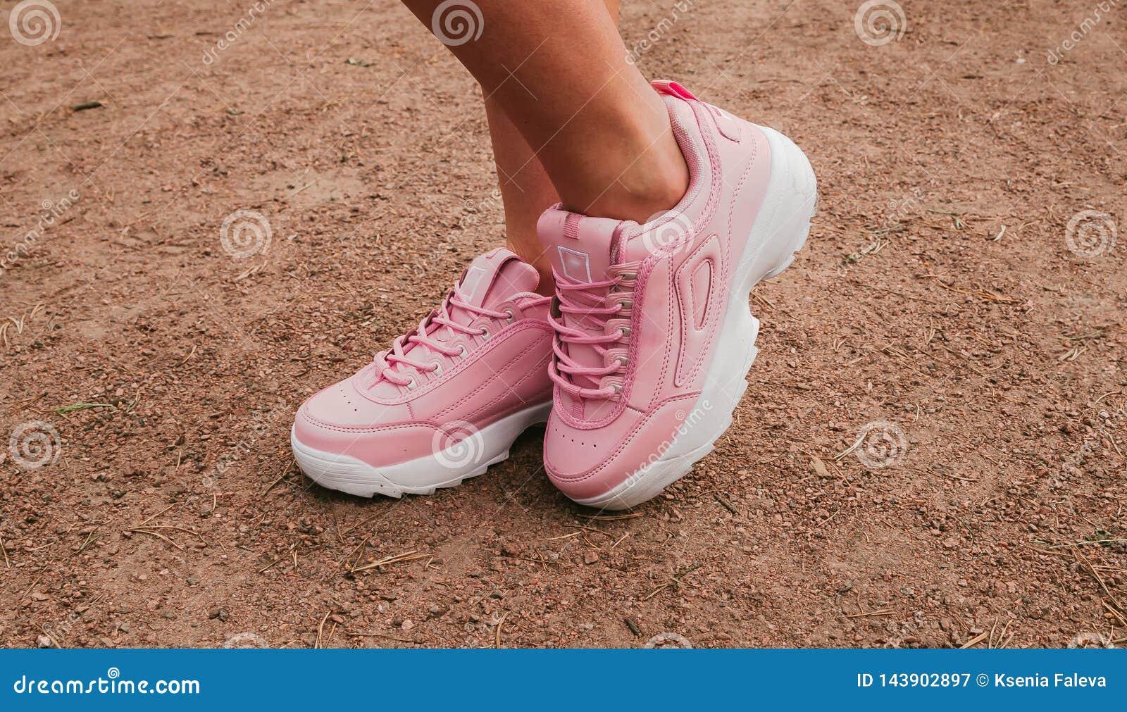 Le scarpe di cuoio delle donne alla moda alla moda di rosa le gambe delle donne con le scarpe da tennis