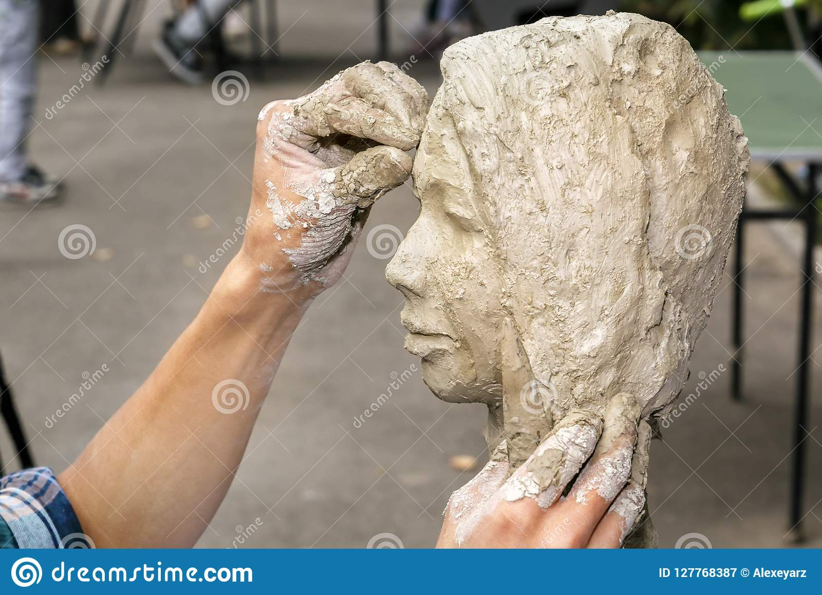 Le sculpteur crée un buste et met son argile de mains sur le squelette de la sculpture