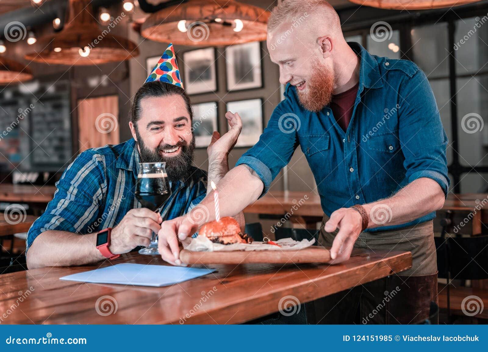 Le sentiment aux cheveux foncés d homme d anniversaire a étonné voir l hamburger bon d anniversaire