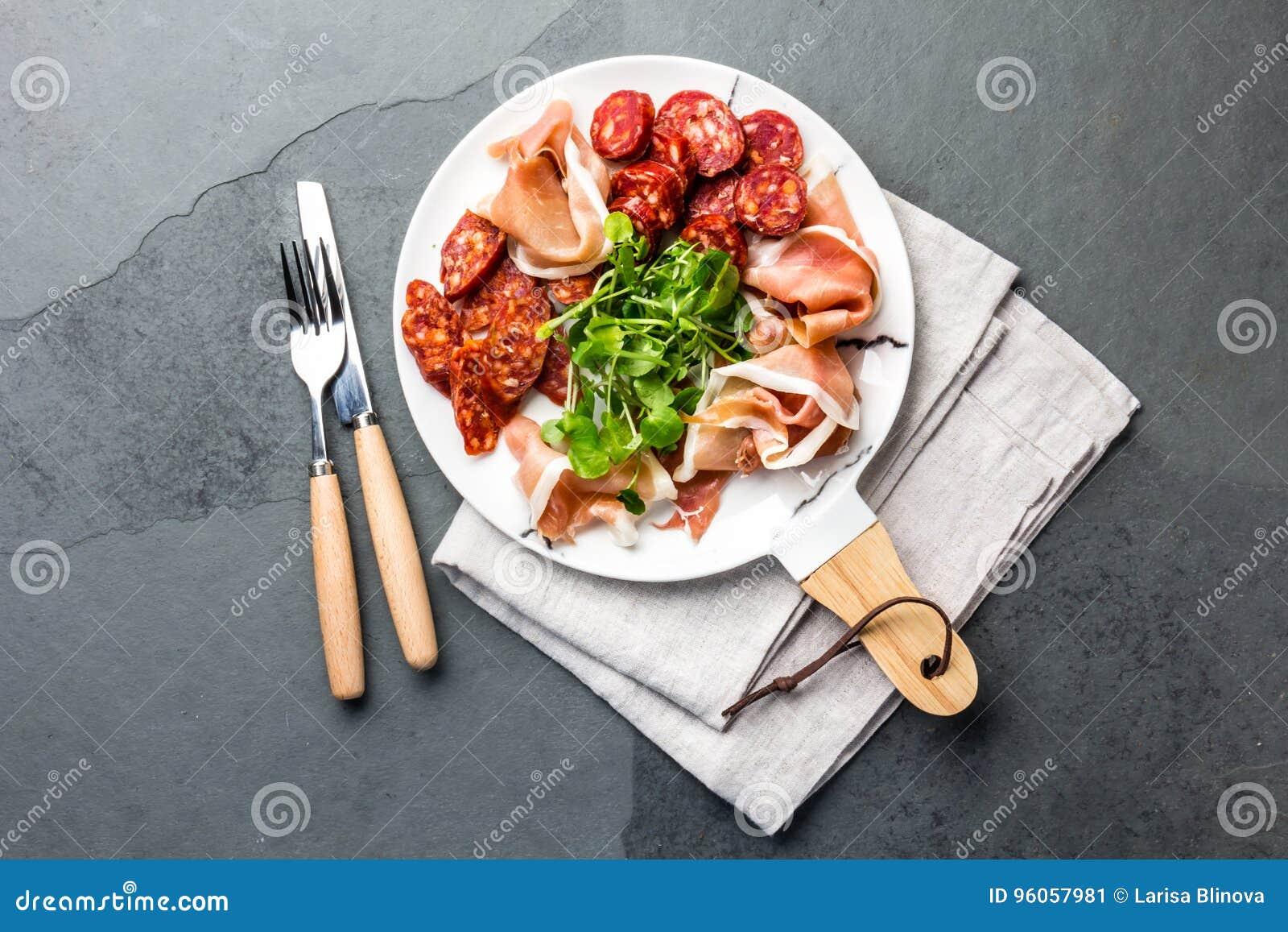 Le serrano et le salami espagnols de jambon sur le blanc ont marbré le plat Vue supérieure