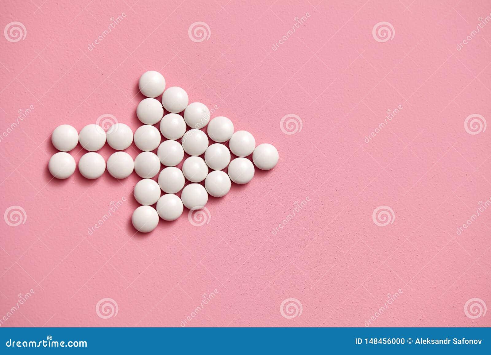 Le signe de flèche est garni des comprimés blancs et ronds sur un fond rose