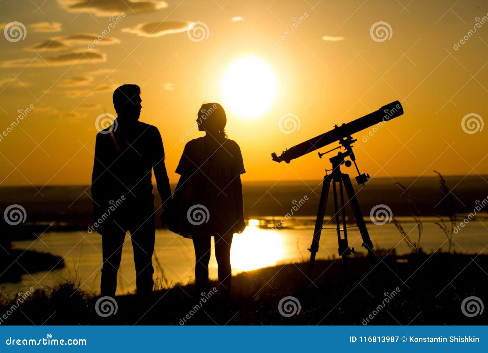Le siluette delle coppie si avvicinano al telescopio sulla collina al tramonto dell estate