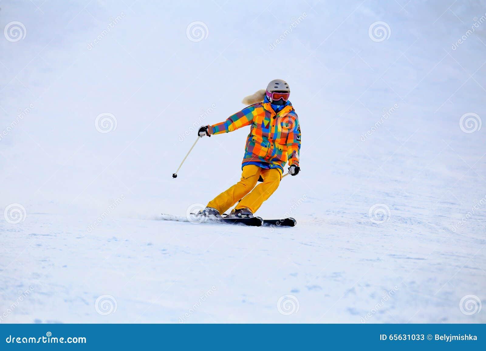 Le skieur dans le masque glisse rapidement tout en skiant de la pente