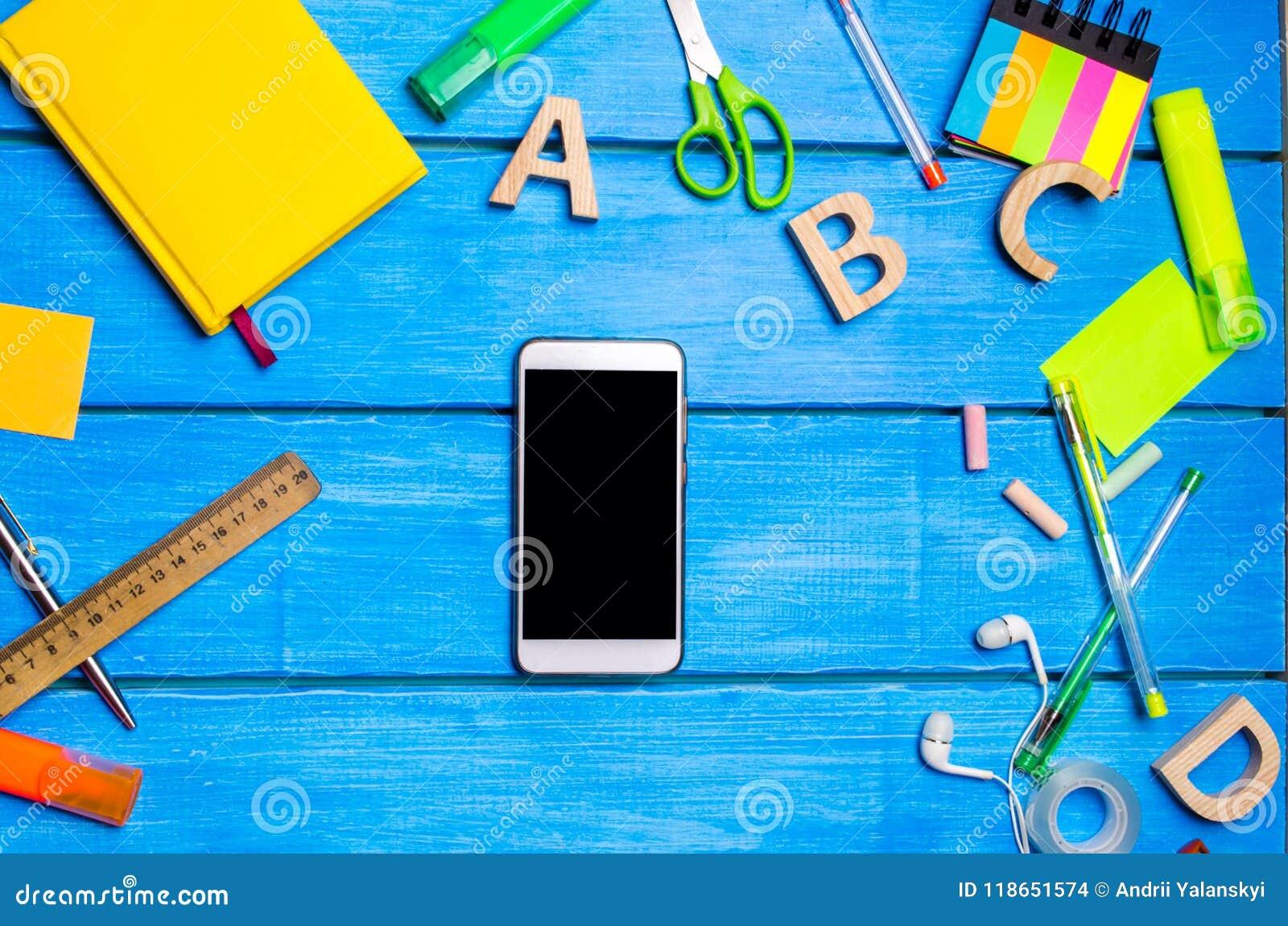 Le smartphone se trouve parmi les fournitures scolaires sur la table en bois bleue de l étudiant Le concept de l étude et de l éd
