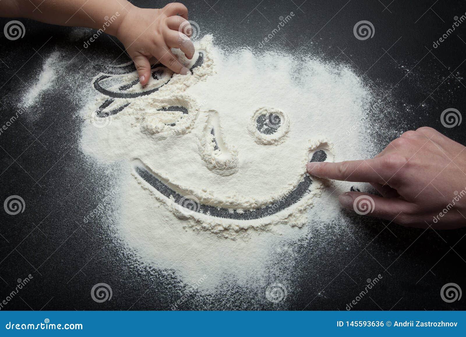 Le smiley de la farine, dessinent une maman de doigt et une fille