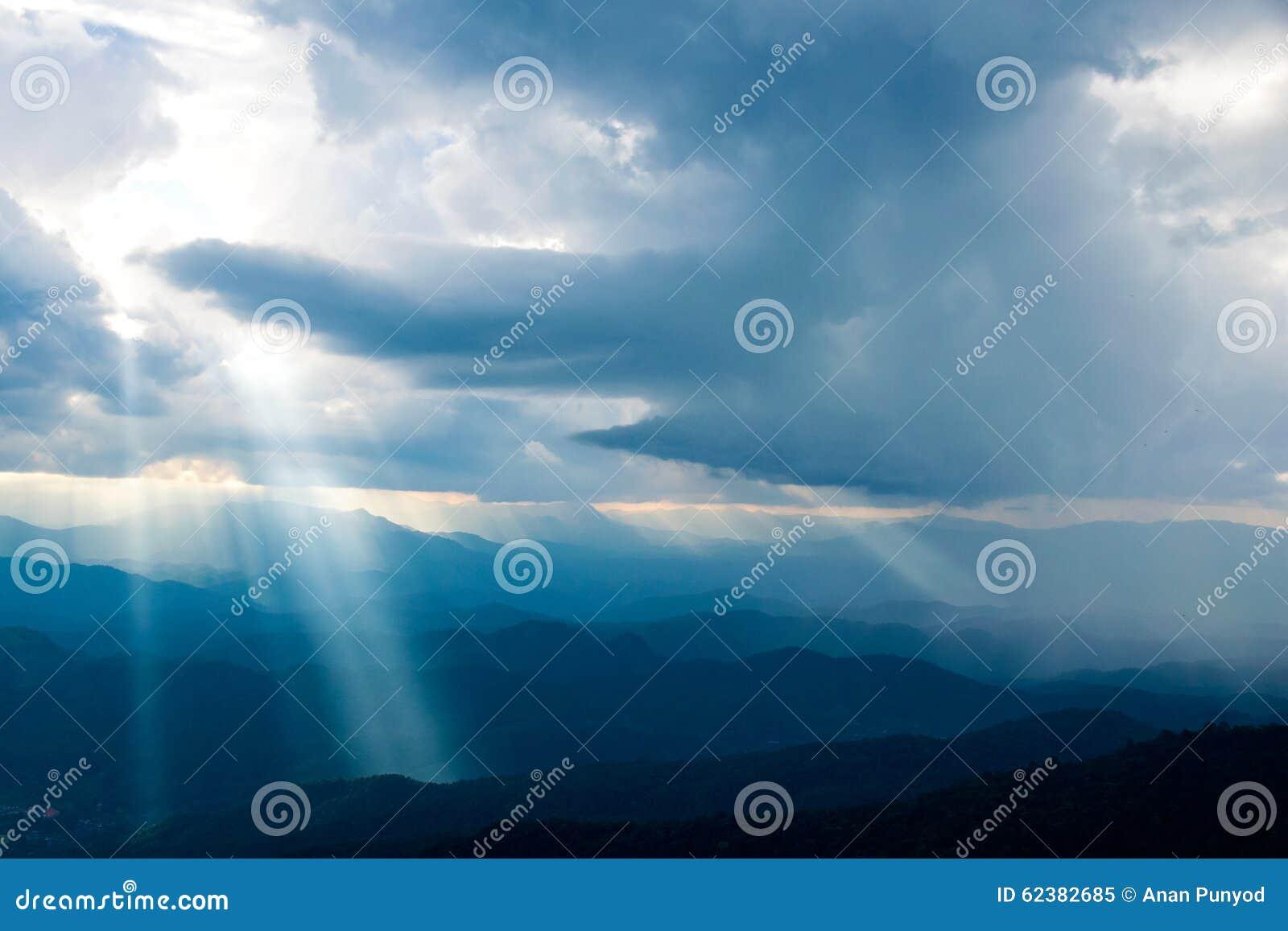Le soleil brillant vers le bas du ciel sur la montagne
