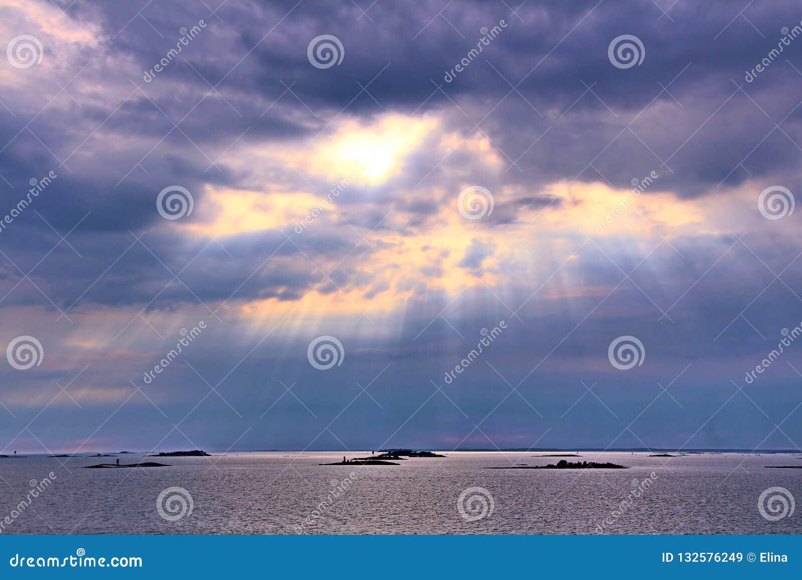 Le soleil derrière les nuages avec des rayons de bas brillant léger sur la mer