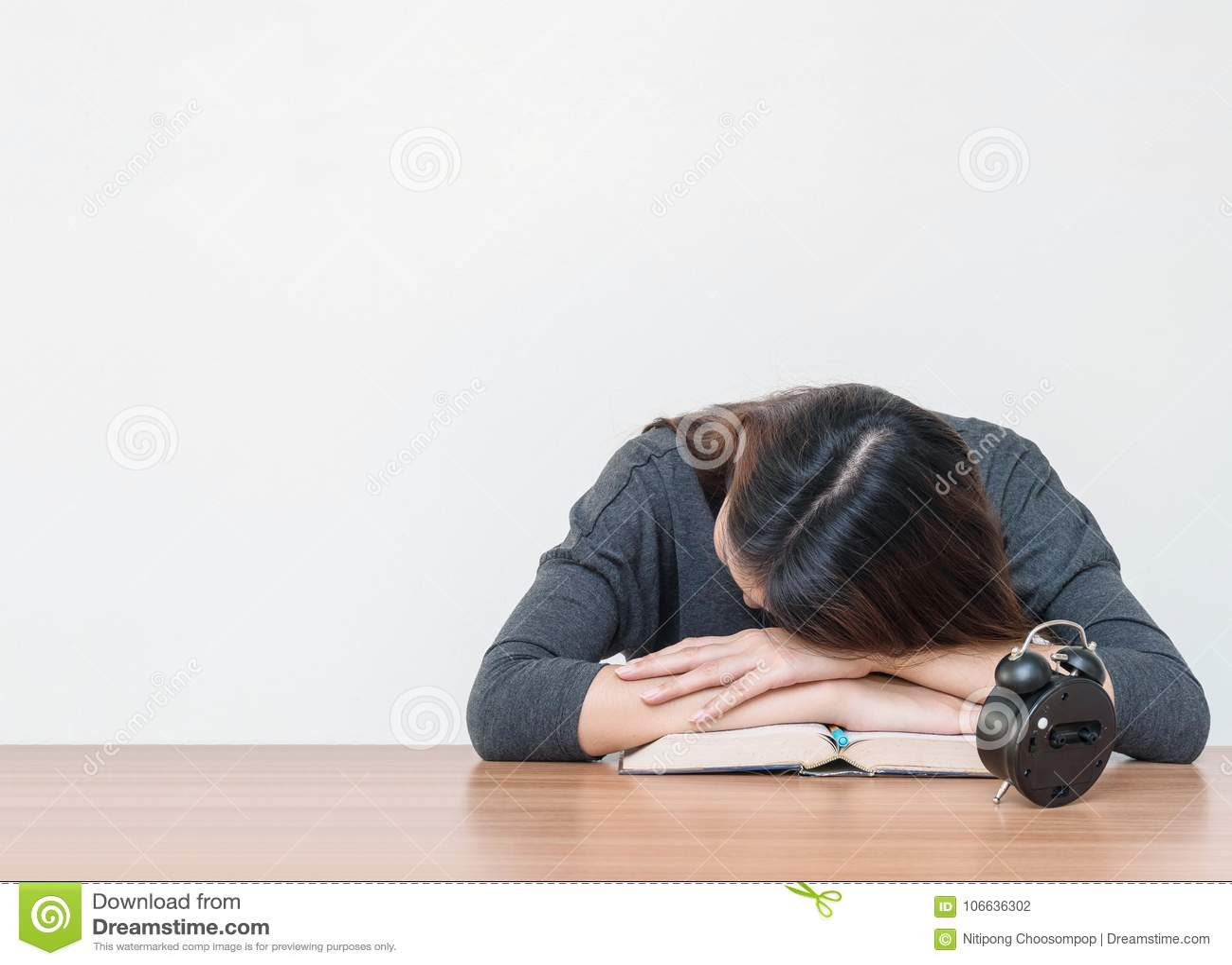 Le sommeil asiatique de femme s est par trouvé sur le bureau après qu elle ait fatigué du livre de lecture sur le bureau en bois