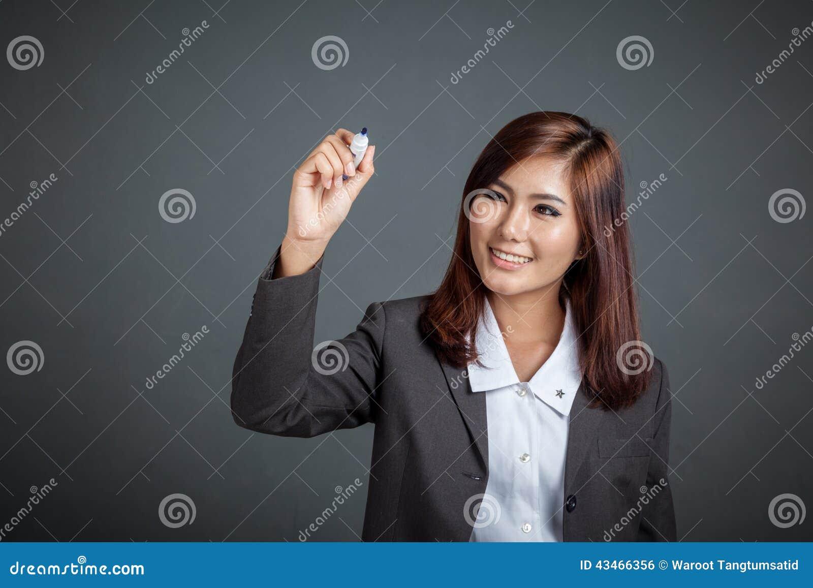 Le sourire asiatique de fille d affaires écrivent dans le ciel