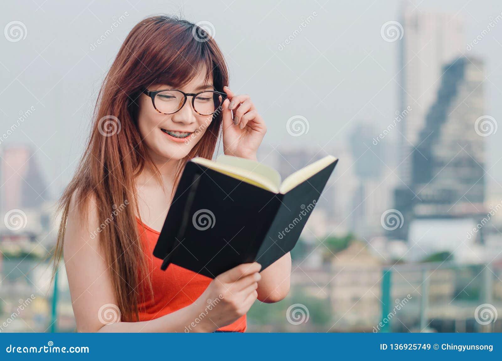 Le sourire jeunes belles des femmes asiatiques en verres lit le livre dans la ville d été