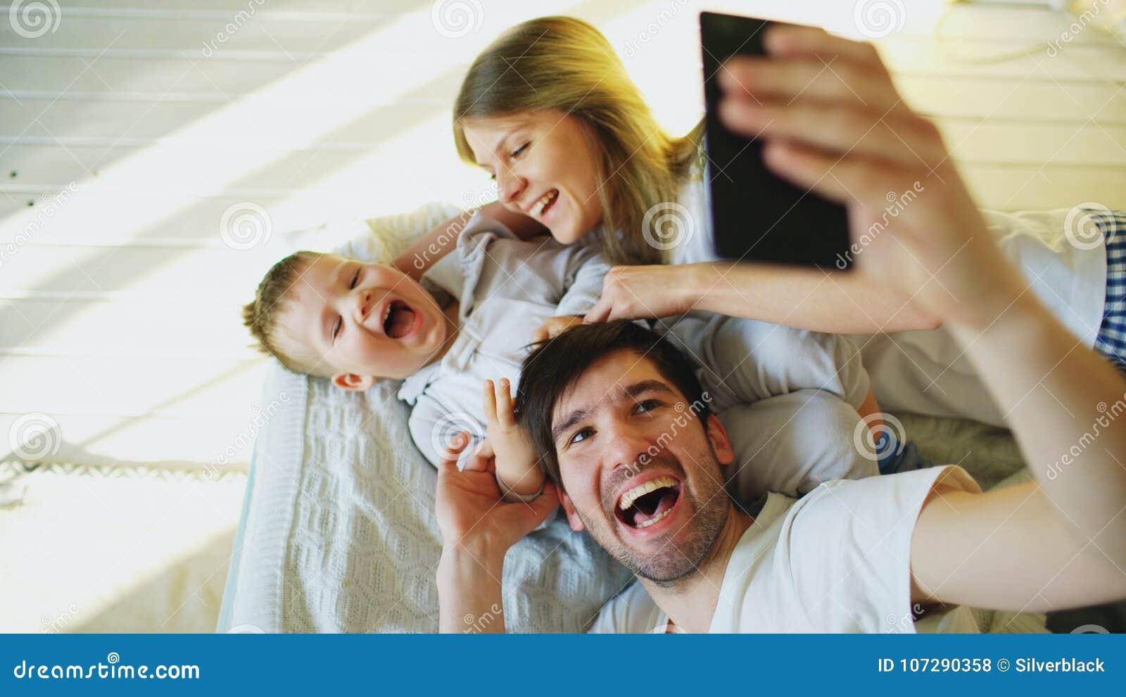 Le sourire parents avec le bébé prenant la photo de famille de selfie sur le lit à la maison