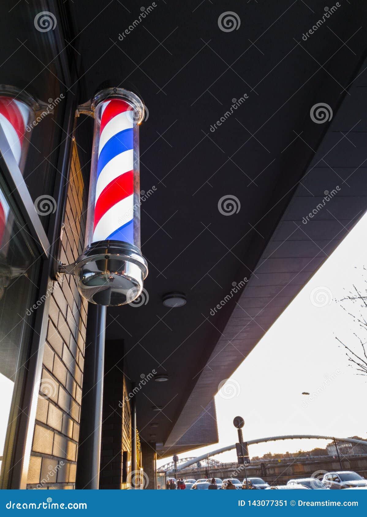 Le spirali bianche, blu e rosse del negozio di barbiere classico firmano a Cracovia