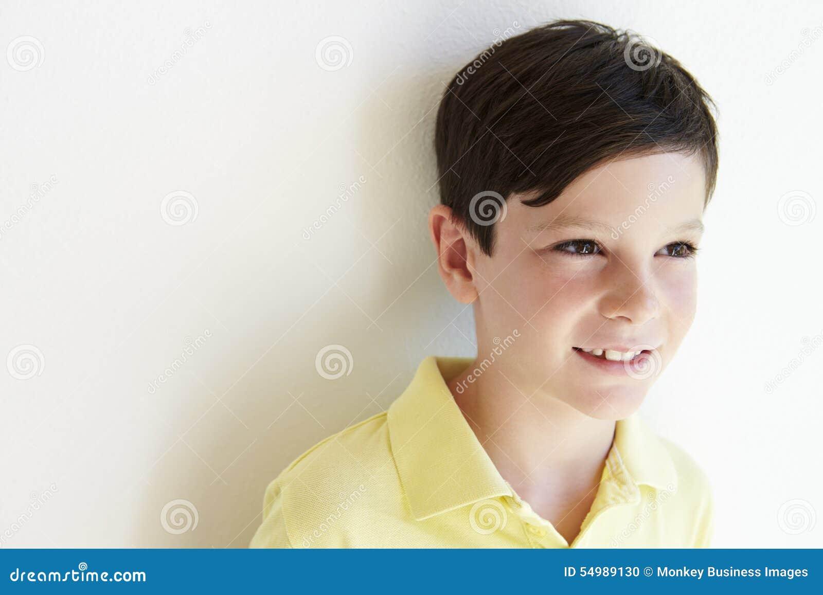 Le stående det fria för ung pojke mot den vita väggen
