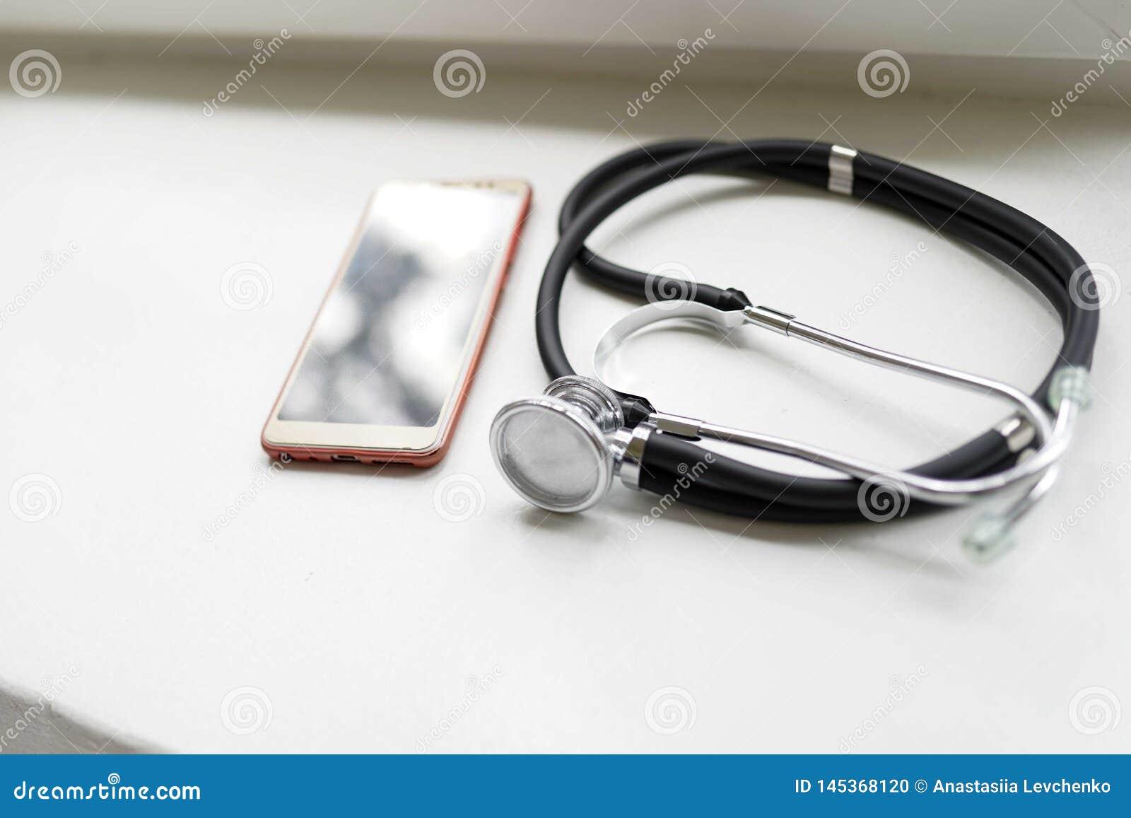 Le st?thoscope et le t?l?phone intelligent mobile sur le fond blanc avec l espace de copie plat s ?tendent Concept m?dical d affa