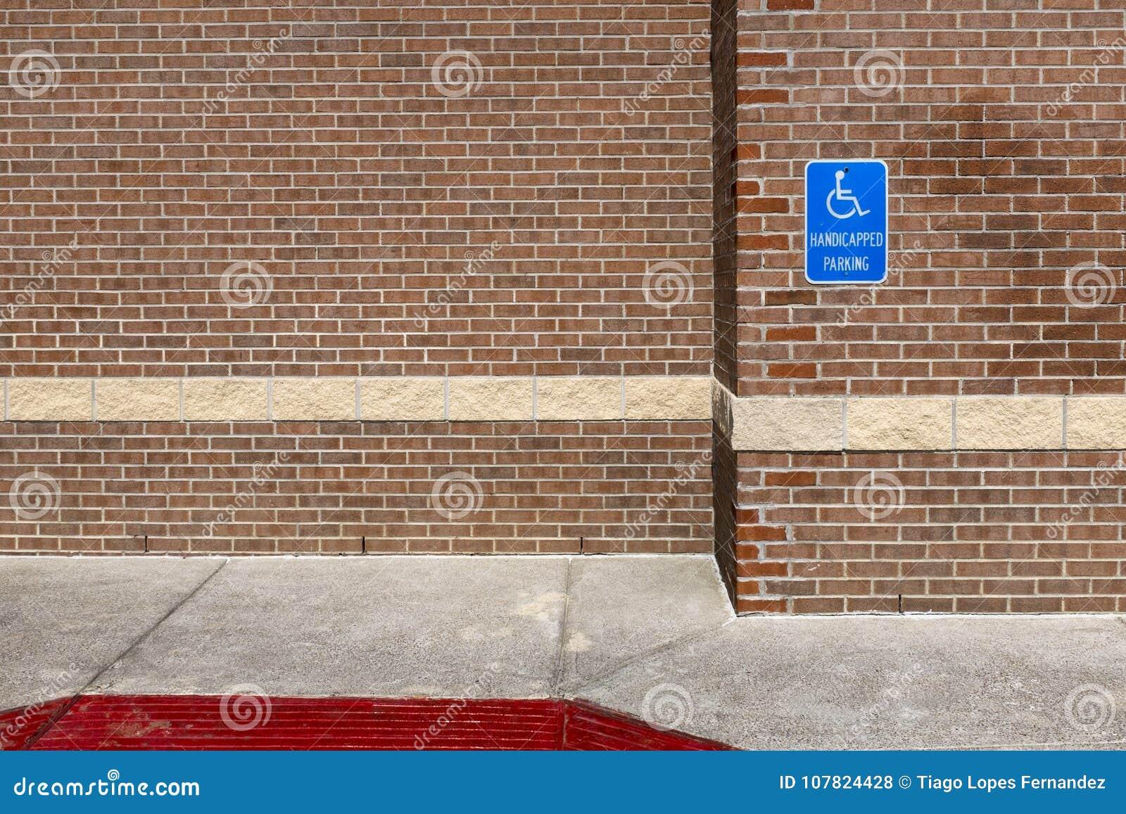 Le stationnement handicapé bleu se connectent un mur de briques