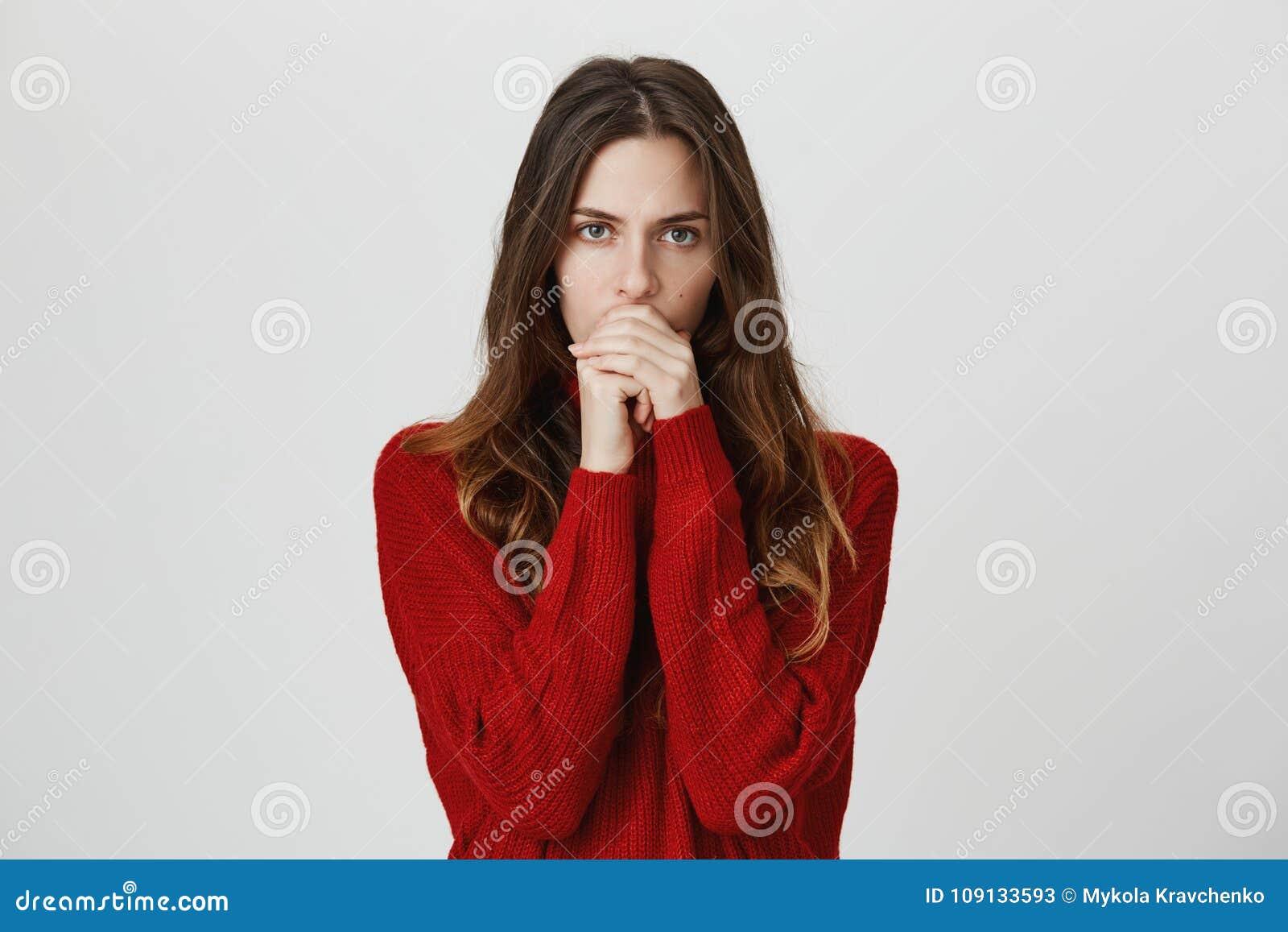 Le studio a tiré de la jeune femelle songeuse sérieuse avec de longs cheveux dans la bouche fermante de chandail rouge, après s ê