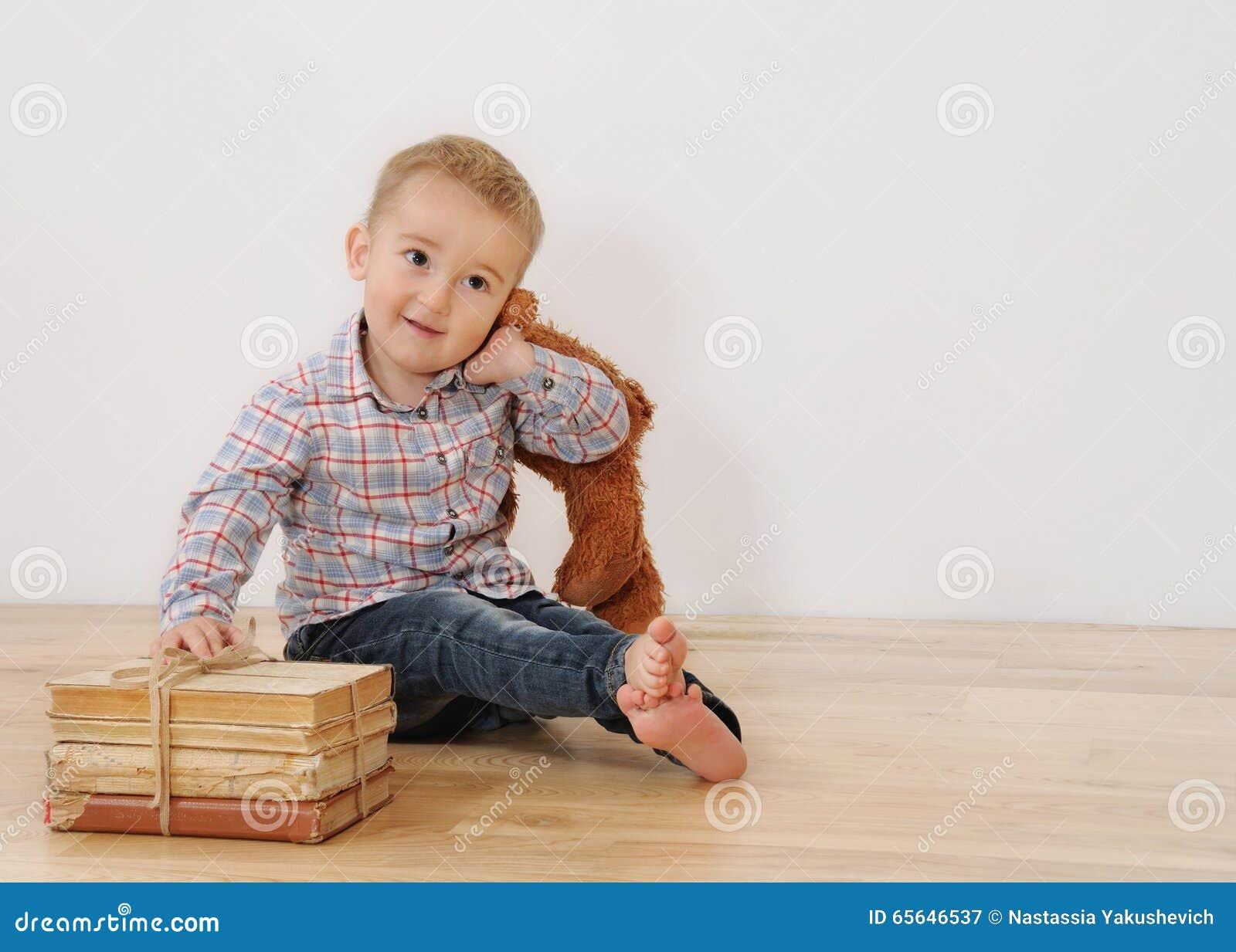 Le studio a tiré du petit garçon de sourire avec son jouet et livres