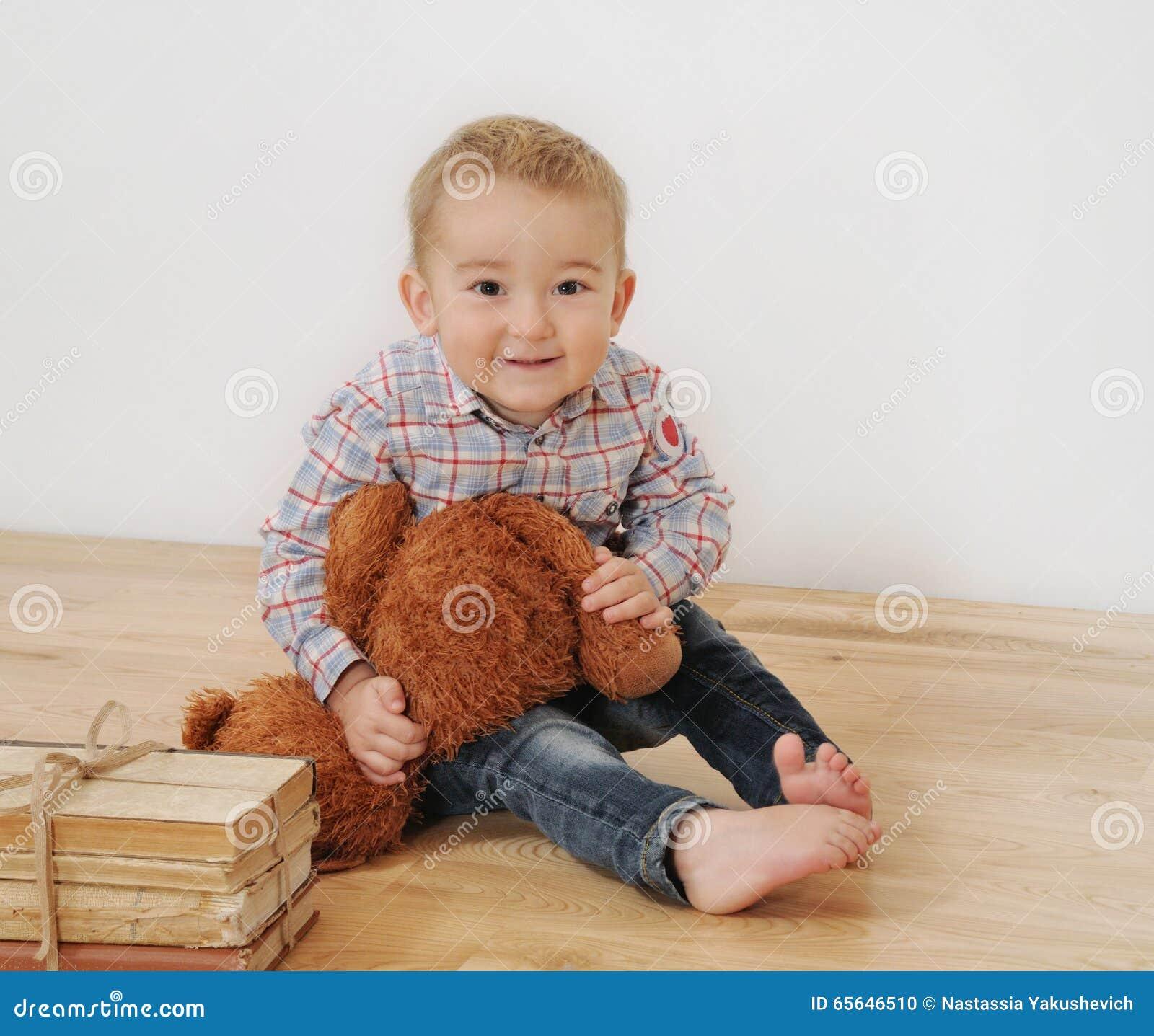 Le studio a tiré du petit garçon de sourire mignon avec son jouet et livres
