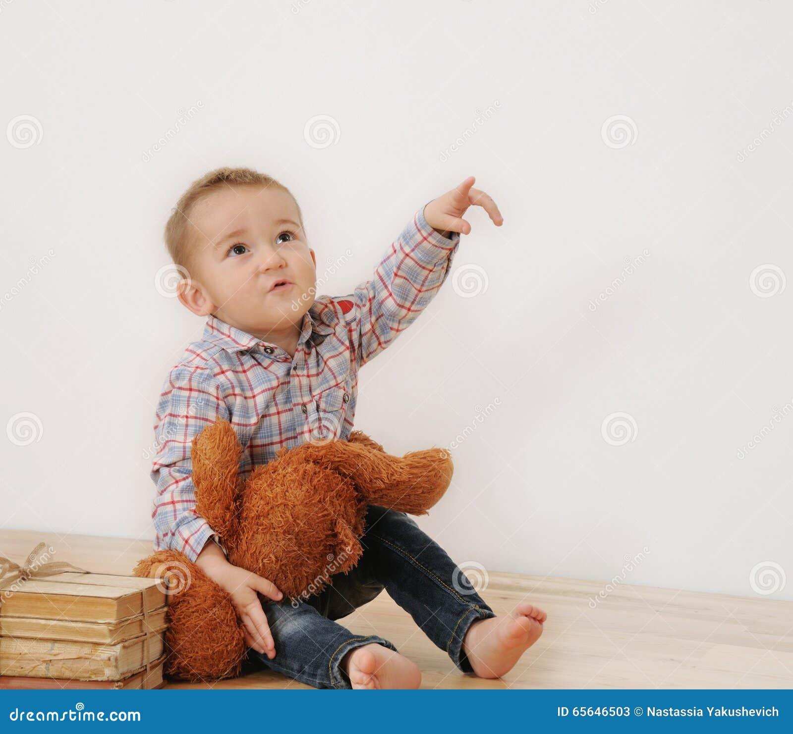Le studio a tiré du point de petit garçon son doigt avec son jouet et livre