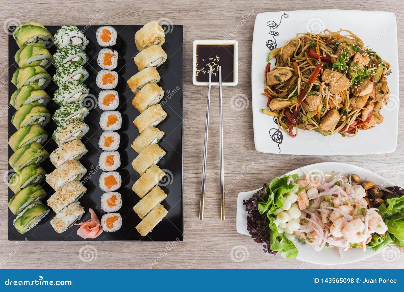 Le sushi roule avec le yakisoba, le ceviche et la sauce de soja sur une table en bois