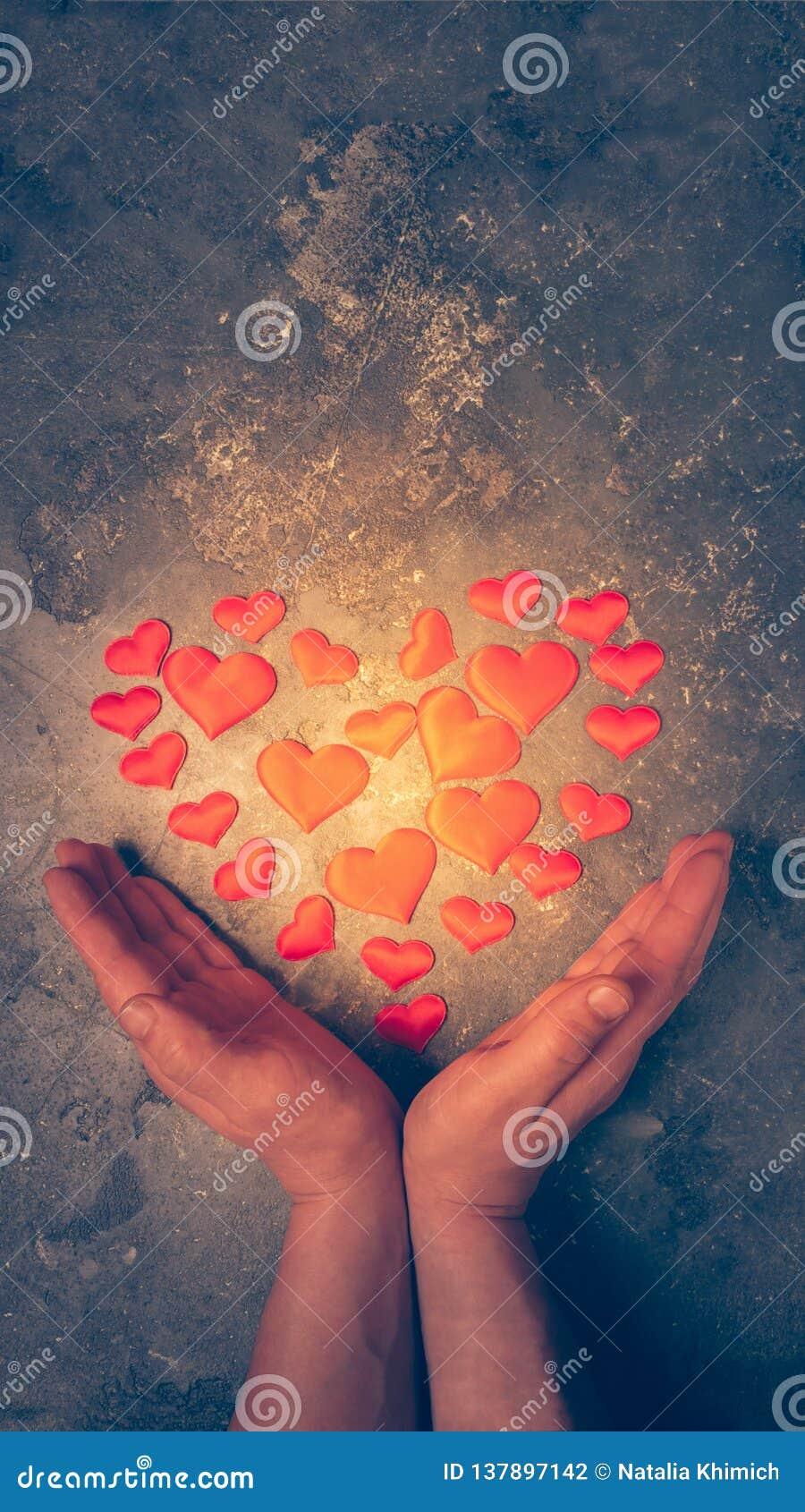 Le symbole de l amour et de la santé est le coeur dans des mains masculines Le coeur brûlant est présenté de petits coeurs dans d
