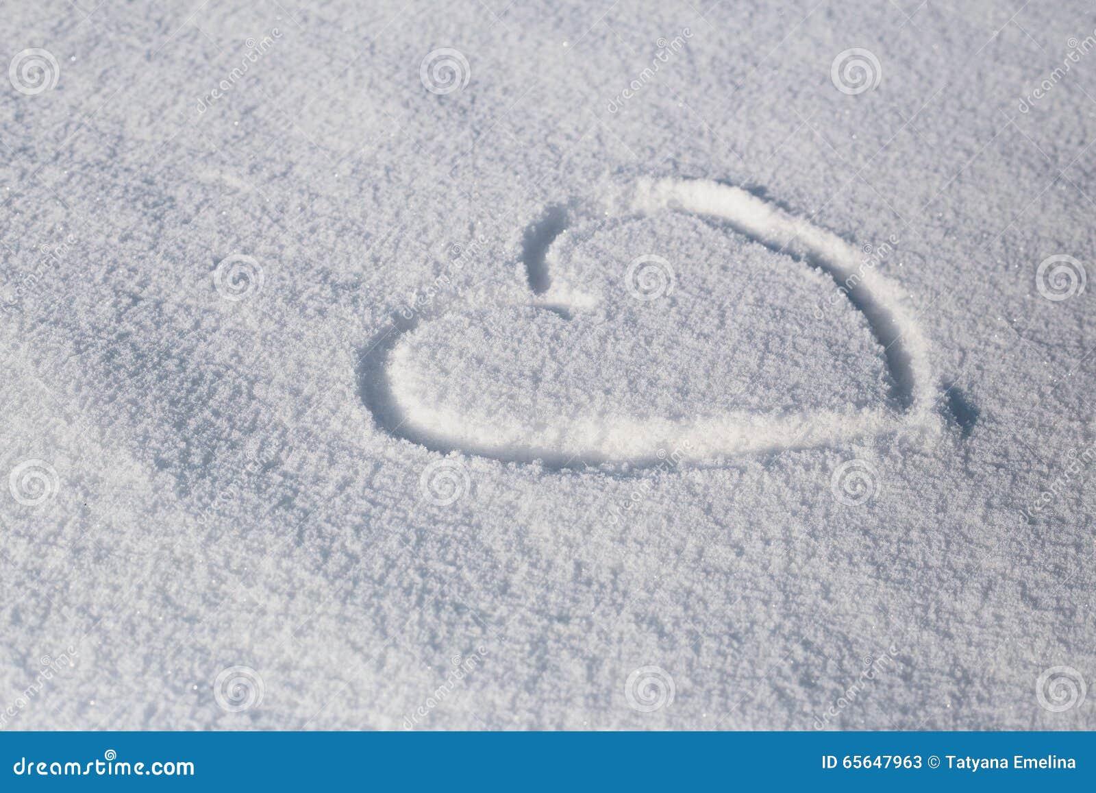 Le symbole du coeur peint sur la neige blanche fraîche