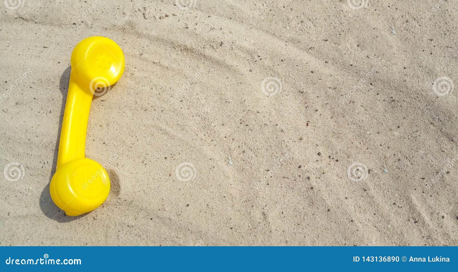 Le téléphone jaune d un vieux téléphone de cru se trouve sur le sable avec un espace de copie pour votre texte avec des contacts