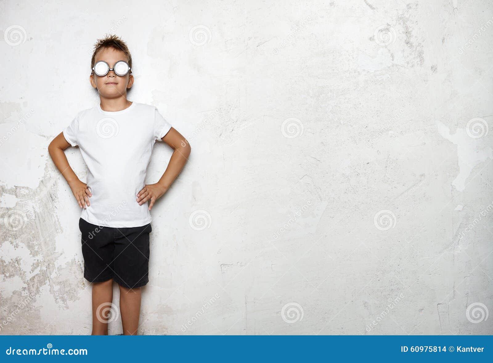 Le T-shirt blanc de port de garçon, court-circuite des supports sur un mur